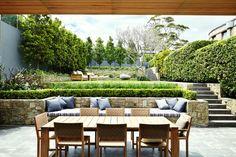 terrasse sur terrain en pente en restanques, murets de soutènement en pierre naturelle et salon de jardin en bois
