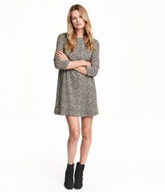Short A-line dress in woven fabric with a printed pattern. Opening at back of neck with button. 3/4-length sleeves, seam at back of waist, and flared, gathered skirt. Unlined.