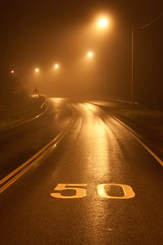 Wet road at night illuminated by glloomy street lights