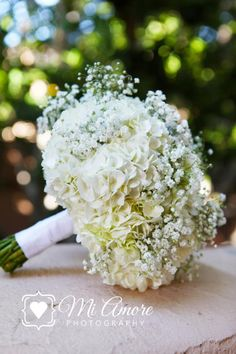 baby's breath and hydrangea bouquet...Like this but maybe a slightly higher proportion of baby's breath and a twine, linen, or more rustic wrap around the stems.