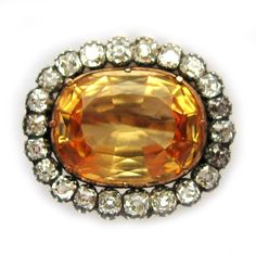 A VICTORIAN OVAL GOLDEN TOPAZ AND DIAMOND CLUSTER BROOCH