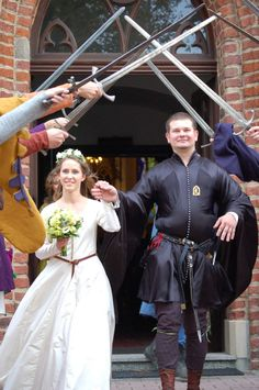 Groomsmen and fathers with swords for bride and groom to walk under after…