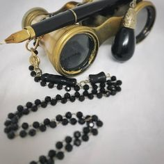 A vintage fountain pen has been used as a pendant on this long black and gold necklace along with an upcycled old (mid-century?) earring repurposed into a charming dangle. All of this hangs from beautiful black glass bead chain with a gorgeous watch fob style clasp. This would make