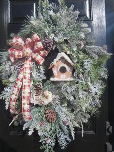This is another of my winter themed wreaths that may be displayed during the Christmas season and be left up through January and February. The focal point is a snow covered icy bird and birdhouse. Both are made of bark and fit it well with farmhouse rustic decor. Many pieces of snow flocked cedar, arborvitae, and iced pine were added throughout the wreath. An XL bow is fashioned from a tan, red and green checked, snowflake embossed patterned 1.5 ribbon. I have used this ribbon on my other…