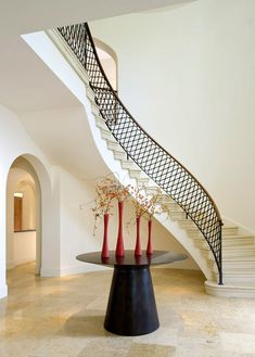 Dramatic, winding, circular staircase with custom iron rails in contemporary, modern style for a Italian Mediterranean Villa entrance and foyer in a Dallas, TX home.
