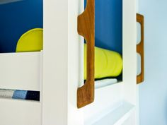 A happy kids' sleeping area at the top of the staircase features both nautical decor and a bright, happy beach-inspired color palette.