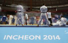 Judoists work out before their judo match at Dowon Gymnasium during the 17th Asian Games in Incheon September 20, 2014. Picture taken with long exposure. (REUTERS/Issei Kato)