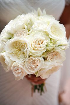 The bride's all-white bouquet of roses and peonies is fresh and ethereal.