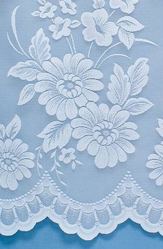 Floral patterned net curtains with an intricate and elegant design.
