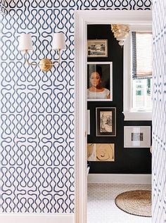 Inside a Fabulously Fresh Nashville Home -- With no room for furniture in the entryway, Gen chose a zingy blue-and-white Cole & Son wallpaper to dress up the space.The wallpaper continues up the stairs to the second-floor landing. Love the geometric blue and white wallpaper, contrasting with the painted black bathroom interior -- such great contrast! See the full home tour of the designers behind Pencil & Paper on our Style Guide!