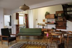 Comfortable Vintage Dining Area And Mid Century Living Room Mixed With Chic Pendant Lamp Above Wide Carpet And Wooden Round Table Plus Chair Near Wooden Shelves And Floral Curtains Combined With Hardwood Floor And Window Treatment: Mid Century Modern Living Room Design Ideas