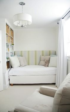 Hide the 2nd twin bed frame and mattress in plain sight by using it to behind the other twin - thus creating a daybed.