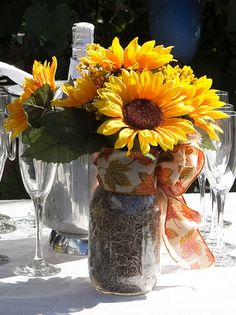 Summer wedding inspiration: sunflowers and and brightly colored bow for this mason jar centerpiece.