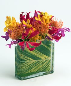 """Tropical Paradise Designed in our rectangular """"envelope"""" vase, this bright and colorful collection of unique blooms like orchids, protea, and gloriosa lilies is a mini burst of paradise!"""