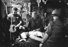 There is little time for cleanliness or relaxation at Charlie Med, the makeshift hospital of Company, 3rd Marine Medical Battalion, handling the wounded at Khe Sanh, Vietnam, March 8, 1968. Doctors, working in the cramped area under continuous battle conditions, make daily life and death decisions in determining the order of who receives treatment for wounds. Using instruments and medicines stored in empty Howitzer cases, Dr. Joseph W. Wolfe, Rutledge, Tenn., center, works on a wounded…