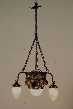 Lampadario del 900. Riccamente lavorato presenta plafoniera centrale e tre bracci con vetri. Quattro punti luce.