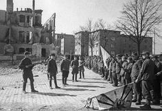 Berlin has fallen. German garrison troops surrender to the Soviets. Note the garrison standard lowered to sweep the ground -- the ultimate gesture of defeat.
