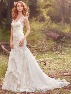 Maggie Sottero - ZALIA, A three-tiered skirt hemmed in scalloped lace appliqués adds romance and whimsy to this classic fit-and-flare. Lace motifs adorn the bodice, illusion V-neckline, illusion straps, and illusion open-back. Finished with covered buttons over zipper closure.