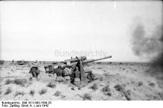 """North Africa, at Bir Hakeim. Firing 88mm anti-aircraft gun. In the background, Colonel General Rommel's infantry fighting vehicle Sd.Kfz. 250 """"Greif""""."""