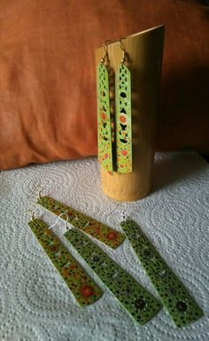 Pendientes hechos a partir de fragmentos de abanico de madera teñida de verde pistacho y decorados a mano con esmaltes de uñas, de Universo Solariana.