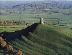 Glastonbury Tor in Somerset, England, with St. The landmark is believed by some to be the Avalon of Arthurian legend. Glastonbury Abbey, Glastonbury England, Glastonbury Somerset, Somerset England, King Arthur, English Countryside, British Isles, Great Britain, Places To See