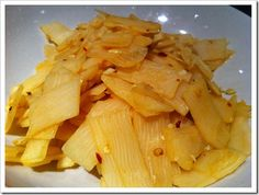 Stir-fried bamboo shoots with red chili flakes and hot sauce.