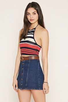 A sweater knit crop top with a striped pattern, scalloped trim, and tasseled self-tie halter straps.