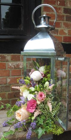 Lantern with cascading flowers including pale pink peony, vuvuzela roses, peach lisianthus, cream spray roses, lavender, ivy and achillea mollis - Bury Court Barn