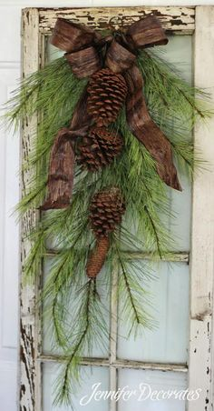 Realistic and rustic door swag adorned with pinecones and a stunning woods inspired ribbon. Perfect addition to a door or window as pictured.