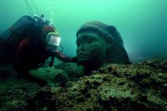 A diver next to the colossal black granite head of Ptolemy XV, the son of...