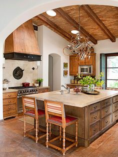 Interior designers often call the ceiling the fifth wall because of its decorating potential. Paying special attention to the span of sheetrock overhead can pay off; not only is it unexpected, but the ceiling can also handle risks that walls and floors cannot. The brick-and-beam ceiling treatment in this Tuscan-style kitchen gives the room a cozy, intimate feel despite its spacious size.