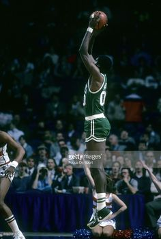 BALTIMORE, MD - CIRCA 1980's: Robert Parish #00 of the Boston Celtics shooting a jump shot against the Washington Bullets during a mid circa 1980's NBA basketball game at the Baltimore Coliseum in Baltimore, Maryland. Parish played for the Celtics from 1980-94.