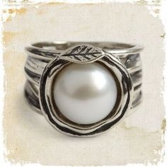 Lily Ring  #RG077  The purity of white and lilies, the earthiness of metal, combined in one poetic ring. A freshwater pearl of radiant beauty sits atop our wide band of antiqued sterling silver, embraced in delicate tendrils. Israel. Whole sizes 5-9