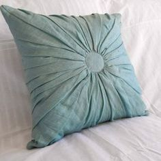 """Linen and cotton-blend throw pillow with gathered center.Product:  PillowConstruction Material: Linen and cotton Color: Ocean        Features: Insert included   Dimensions: 18"""" x 18""""      Cleaning and Care: Machine washable"""