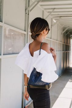 Pam Hetlinger wearing a White Ruffle Top styled with black ripped jeans and velvet pumps.