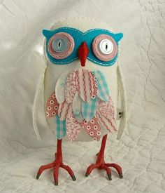 "White wool felt owl with pretty print aqua, red, and pink feathers.  - Feathers lined with vintage fabric.  - Vintage button eyes  - 6.5"" tall  - Hand sewn  - Filled with Polyfil and wool scraps.  - Legs are wire wrapped with Floratape."