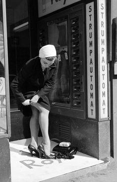 A woman hikes up her new nylons in Stockholm, Sweden c.1956 I wish these automats would still exist.