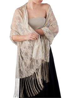 """Look stunning in this beige lace evening shawl with a subtle silver over spray on the flower details. This shawl is made in Venice with a fine net and flower motif with elastin added for a stretchy feel. Hand knotted 8"""" fringe."""