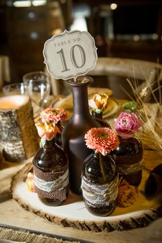 Rustic centerpiece- love the flower bottles around , but i would put a nice tree piece with simple flowers . maybe some orchids .