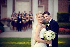 Bride/groom posing with wedding party out of focus