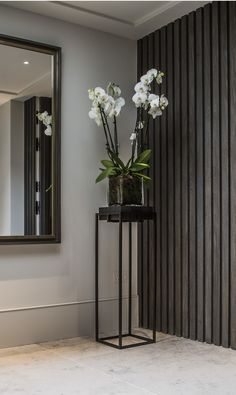 Serene and elegant plant stand and orchid in Bedford Gardens interior designed by De Salles Flint.