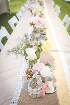 Pink flowers in a jar on a table runner as centrepieces