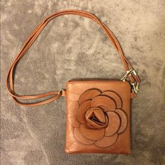 Small Brown Purse Flower decal on front, big pocket and mini inner pocket. Zip closure. Strap can be worn long or doubled to be short. Great as a crossbody. Never been worn - still has foam padding inside Bags Mini Bags