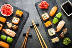 Sushi and sushi roll set on black stone table top view by Nadia-nb on @creativemarket