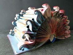 """Livre-objet """"Le soleil rouge"""". Il s'agit d'un vieux livre dont les pages ont été restructurées par pliage et découpage afin de lui donner une forme en 3 dimensions. Taille : 32,5 x 21,5 x 17 cm."""