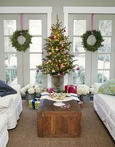 Table-top Christmas tree in urn and wreaths hung in the windows by ribbon.