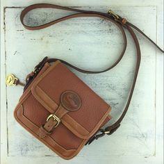 """[Vintage] Dooney & Bourke Crossbody Leather Cognac Classic vintage crossbody bag. All-weather leather. Pebbles texture. Duck logo on front with buckle closure. Inside has a zip pocket and 2 card pockets. Made in U.S.A.  Dimensions: 6"""" Wide x 5.5"""" Tall x 2.5"""" Deep Strap Drop: 20"""" on the shortest hole Condition: EUC. Slight wear on edges. No major flaws. Inside is very clean.  No Trades! Dooney & Bourke Bags Crossbody Bags"""