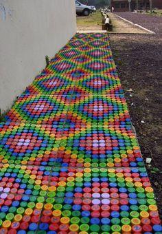 Вместо скучной грунтовой дорожки на даче можно сделать радужную или мозаичную. Лучше, если она затенена - так крышки не выцветут очень долго