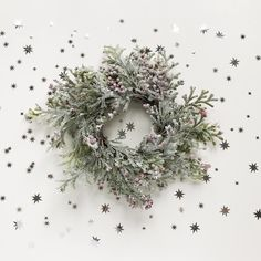 Picture of a Christmas Wreath surrounded by tiny shiny stars and glitter. Photo by lelia_milaya on Twenty20