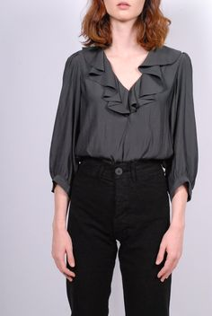 Smythe Over The Head Ruffle Blouse in Carbon. Moderately tailored, this over-the-head blouse features a deep V ruffle neckline and shirttail hem. Fabric Polyester Fit True to size Dry Clean Imported Sale items are final sale. Essential Wardrobe Pieces, Tailored Jacket, Product Launch, Ruffle Blouse, Menswear, Fabric, Tops, Women, Products